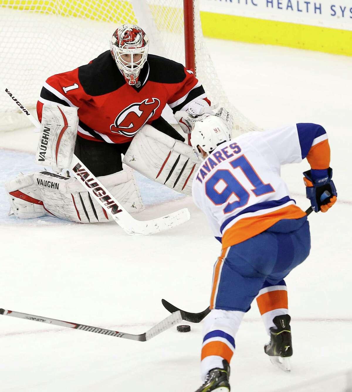 New York Islanders center John Tavares (91) scores a game-winning goal against New Jersey Devils goalkeeper Keith Kinkaid (1) during overtime of an NHL hockey game, Friday, Jan. 9, 2015, in Newark, N.J. The Islanders won 3-2. (AP Photo/Julio Cortez) ORG XMIT: NJJC124