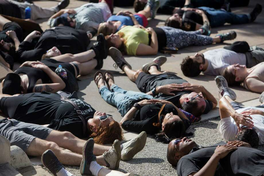 """Dozens of people participate in a """"die-in"""" to remember those who have lost their lives to police this year during a rally hosted by Black Lives Matter Austin at the Texas State Capitol in Austin, Texas on September 19, 2015. Photo: Carolyn Van Houten, Staff / San Antonio Express-News / 2015 San Antonio Express-News"""