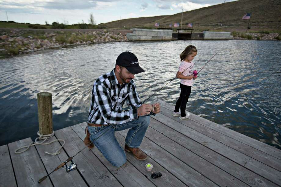 Andy Johnson and his daughter ,Aspen, 6, fish in a pond he created by damming a small creek running through his property, in Fort Bridger, Wyo. The Environmental Protection Agency believes that Johnson's creation of the pond violates the Clean Water Act. Photo: KIM RAFF, STR / NYTNS