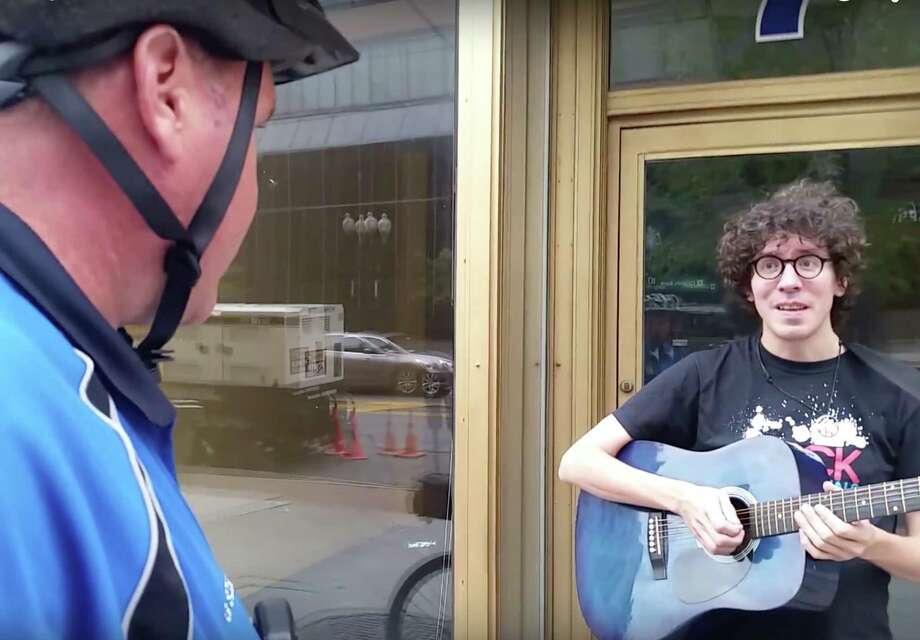 In a video posted on Youtube, musician Leif Solem is told by Albany Officer Glenn Szelest that he is not allowed to perform on the sidewalk without a permit. Solem was playing on North Pearl Street standing in the doorway of an empty storefront when he was accused, by Officer Szelest, of impeding foot traffic. (Cat Jones via Youtube) ORG XMIT: MER2015091415294508