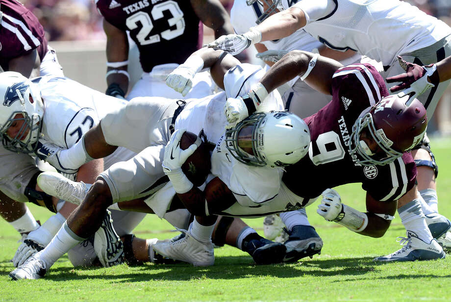 Texas A&M's Qualen Cunningham (9) throws down Nevada running back Don Jackson (6) for a loss during the first half of an NCAA college football game Saturday, Sept. 19, 2015, in College Station, Texas. (Sam Craft/College Station Eagle via AP) MANDATORY CREDIT Photo: Sam Craft, MBR / Associated Press / College Station Eagle