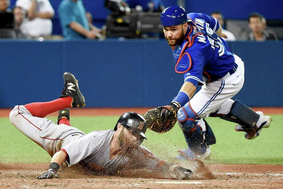 Boston Red Sox second baseman Dustin Pedroia, left, slides safe past Toronto Blue Jays catcher Russell Martin, right, to take the lead during the ninth inning of a baseball game, Saturday, Sept. 19, 2015 in Toronto.  Boston won 7-6. (Nathan Denette/The Canadian Press via AP) MANDATORY CREDIT ORG XMIT: NSD108 Photo: Nathan Denette / CP