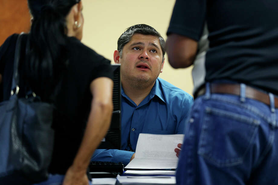Cameron County Veterans Services Director Salvador J. Castillo helps out a veteran at his offices in Brownsville, Texas, Wednesday, July 22, 2015. Castillo is charged with helping military veterans with benefits due to them through the Veterans Department. Photo: JERRY LARA, Staff / San Antonio Express-News / © 2015 San Antonio Express-News