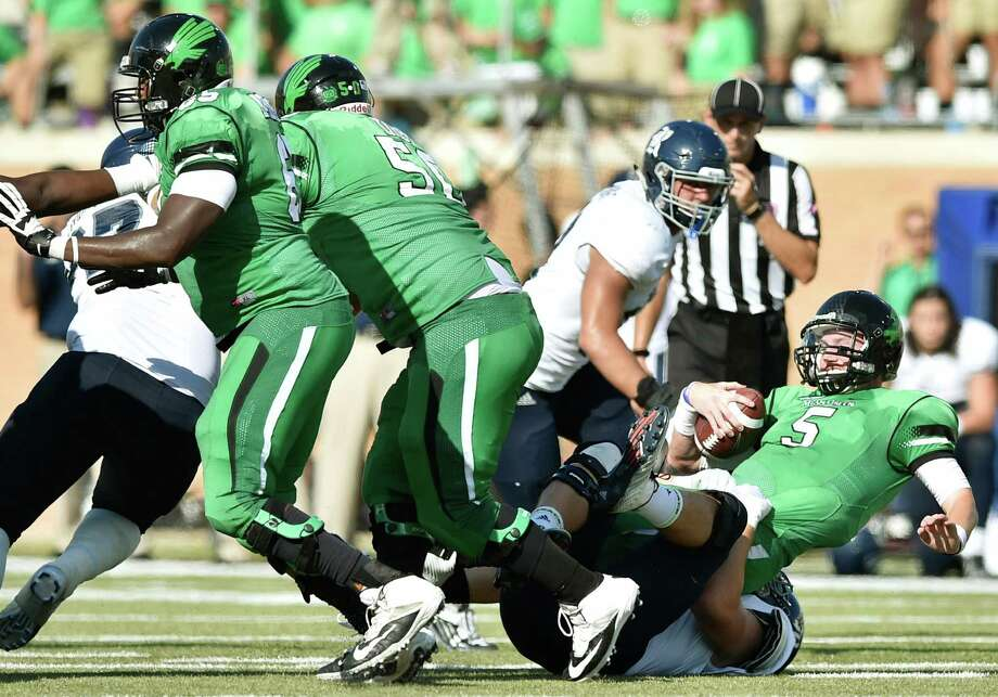North Texas quarterback Andrew McNulty (5) had his hands full against Rice's defense, taking a tumble on this sack by Rice defensive end Parker Hanusa. Photo: David Minton, Staff Photographer / Denton Record-Chronicle