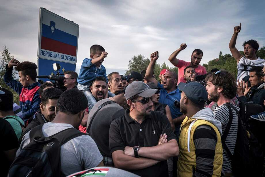 Queued for hours and growing impatient, refugees chant slogans waiting to cross the border into Slovenia in Harmica, Croatia, Sept. 19, 2015. The many thousands of migrants who entered Croatia since Wednesday had been essentially trapped there, but now hoping to move on to Slovenia, whose laws — unlike Croatia — allow for free movement between European Union members. (Sergey Ponomarev/The New York Times) ORG XMIT: XNYT32 Photo: SERGEY PONOMAREV / NYTNS