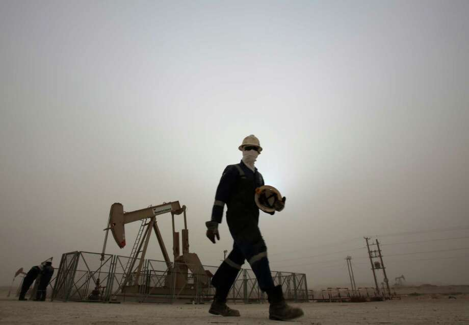 FILE - In this Thursday, Jan. 8, 2015 file photo, an oil worker walks by an oil pump during a sandstorm that blew in, in the desert oil fields of Sakhir, Bahrain. Across a Mideast fueled by oil production, low global prices have some countries running on empty and scrambling to cover shortfalls, even as more regional crude is on tap to enter the market.(AP Photo/Hasan Jamali, File) ORG XMIT: CAIMA505 Photo: Hasan Jamali / AP