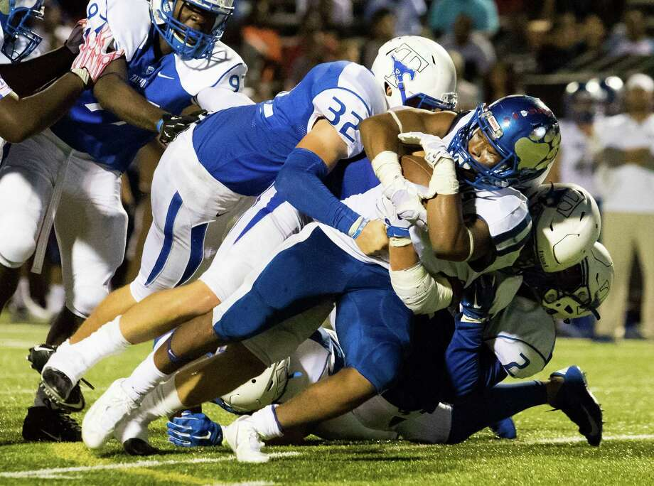 West Brook's Joel Denly (29) is tackled at the line of scrimmage by a handful of Taylor defenders late in the fourth quarter at Rhodes Stadium on Saturday, Setember 19, 2015, in Katy. Photo: Joe Buvid, For The Chronicle / © 2015 Joe Buvid