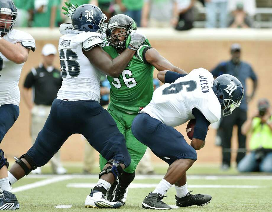 North Texas junior defensive end Malik Dilonga (56) gets a hand on Rice senior quarterback Driphus Jackson (6) while holding back freshman offensive lineman Calvin Anderson (66) on Sept. 19, 2015, at Apogee Stadium in Denton. Photo: David Minton, Denton Record-Chronicle / Denton Record-Chronicle