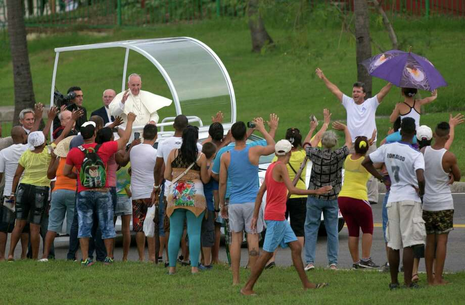 Pope Francis waves from his popemobile on his way from the airport to Havana, Cuba, Saturday, Sept. 19, 2015. Pope Francis began his 10-day trip to Cuba and the United States, embarking on his first trip to the onetime Cold War foes after helping to nudge forward their historic rapprochement. (Ismael Francisco/Cubadebate Via AP) ORG XMIT: XEM228 Photo: Ismael Francisco / Cubadebate