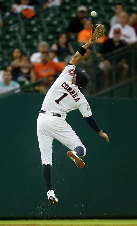 Astros shortstop Carlos Correa makes a leaping, over-his-shoulder catch of a blooper to shallow left field by Oakland's Jake Smolinski in the fourth inning Saturday night. Photo: Karen Warren, Staff / © 2015 Houston Chronicle