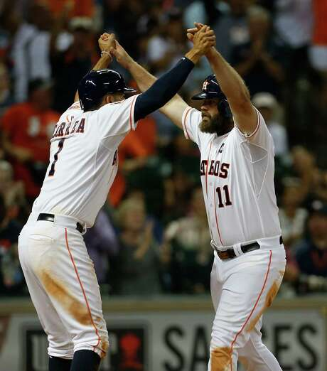 Evan Gattis, right, gave the Astros and teammate Carlos Correa a much-needed lift with a three-run homer in the seventh. Photo: Karen Warren, Staff / © 2015 Houston Chronicle