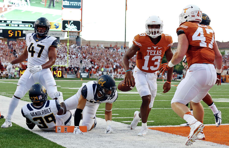 Texas Longhorns' quarterback Jerrod Heard (center) celebrates with teammate Texas Longhorns' tight end Andrew Beck after scoring a touchdown against the California Golden Bears during first half action Saturday Sept. 19, 2015 at Texas Memorial Stadium in Austin, Tx. Photo: Edward A. Ornelas, San Antonio Express-News / © 2015 San Antonio Express-News