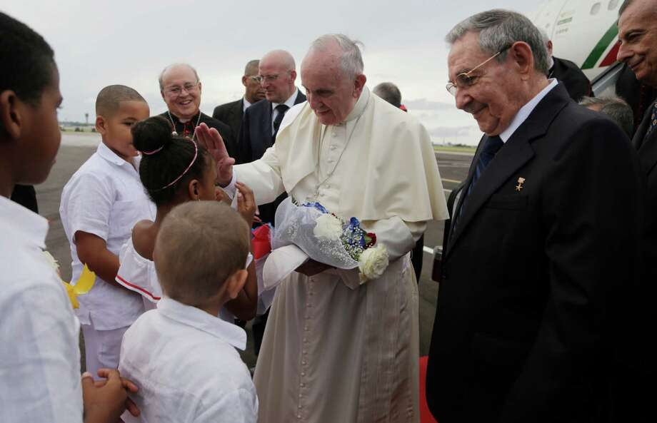 Pope Francis blesses a girl as Cuba's President Raul Castro looks on after landing at the airport in Havana, Cuba, Saturday, Sept. 19, 2015. Pope Francis began his 10-day trip to Cuba and the United States, embarking on his first trip to the onetime Cold War foes after helping to nudge forward their historic rapprochement.(Ismael Francisco/Cubadebate Via AP) Photo: Ismael Francisco, STR / Cubadebate
