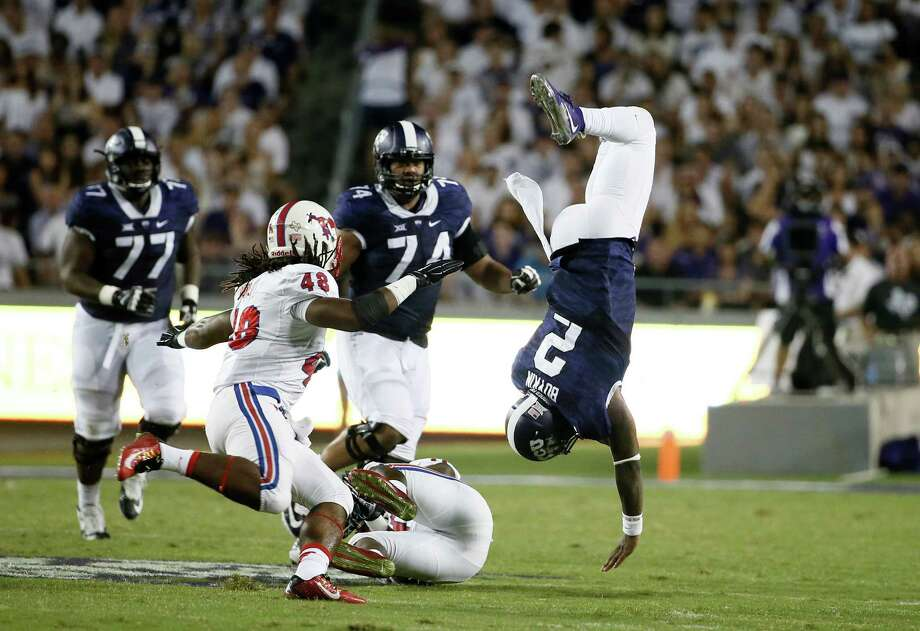 TCU quarterback Trevone Boykin (2) is upended by SMU's Kyran Mitchell, bottom, as Anthony Rhone (48), offensive tackle Halapoulivaati Vaitai (74) and guard Jamelle Naff (77) watch in the first half of an NCAA college football game Saturday, Sept. 19, 2015, in Fort Worth, Texas. (AP Photo/Tony Gutierrez) Photo: Tony Gutierrez, STF / AP