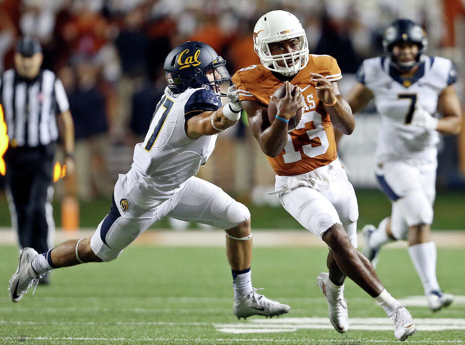 Texas Longhorns' quarterback Jerrod Heard looks for room around California Golden Bears' safety Luke Rubenzer late in the game Saturday Sept. 19, 2015 at Royal-Memorial Stadium in Austin. Heard scored a touchdown on the run. The California Golden Bears won 45-44. Photo: Edward A. Ornelas /San Antonio Express-News / © 2015 San Antonio Express-News