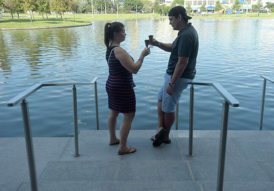 Cheryl Ricks and Josh LeBlanc toast one another as they sample brews by the lake at the first Craft Beer Festival Saturday at the Event Centre. The City of Beaumont teamed up with local distributors Giglio and 2-Row to put on the event, which featured craft beers from over 30 breweries. Photo taken Saturday, September 19, 2015 Photo by Kim Brent Photo: Kim Brent / Beaumont Enterprise