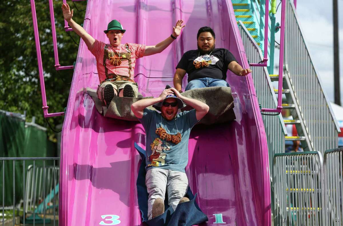Paul Reich, David Allen and Dennis Phrasavath cruise down a slide during Fremont Oktoberfest on Saturday, September 19, 2015. The annual three day event climates in a Sunday Oktoberfest 5k and chainsaw pumpkin carving contest.