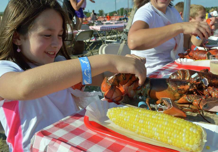 Molly Oliver, 8, of Westport digs in to her lobster and corn Saturday at the Westport Library's 4th annual LobsterFest at Compo Beach. Photo: Jarret Liotta / For Hearst Connecticut Media / Westport News
