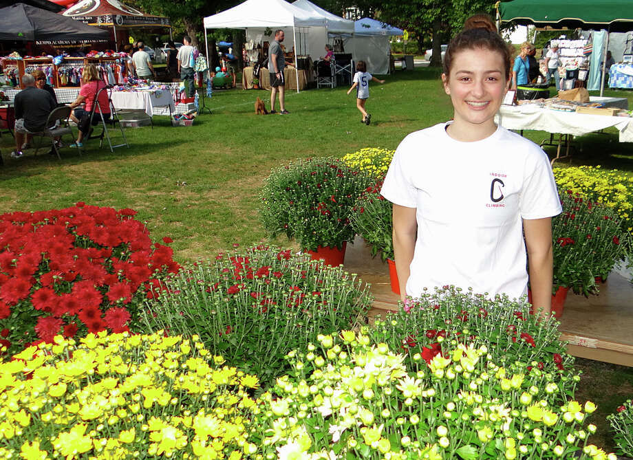 Theodora Hurley, 17, Fairfield Ludlowe High School's Key Club president, sells mums at the 24th annual Fairfield Kiwanis Fall Juried Arts & Crafts Fair on Town Hall Green. Photo: Mike Lauterborn / For Hearst Connecticut Media / Fairfield Citizen