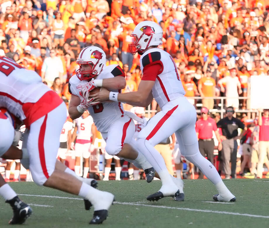 Carson Earp, 11, gives the ball to Kade Harrington, 8, during the game between the Lamar Cardinals and the Sam Houston State Bearkats at Bowers Stadium in Huntsville, Saturday night, September 19th, 2015 - photo provided by Kyle Ezell
