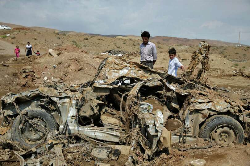 Iranians look at the wreckage of a vehicle after a flash flood in ...