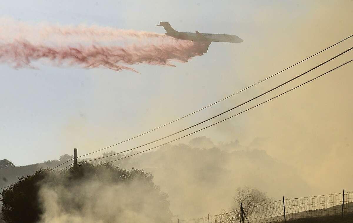 A plane drops fire retardant on a fire along Highway 68 east of Laureles Grade in rural Salinas, Calif., Saturday, Sept. 19, 2015. (David Royal/The Monterey County Herald via AP) MANDATORY CREDIT