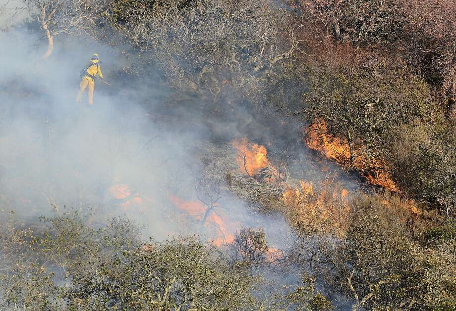 Brush and oak trees flare up as firefighters work to contain a blaze that burns along Highway 68 east of Laureles Grade in rural Salinas, Calif., Saturday, Sept. 19, 2015. (David Royal/The Monterey County Herald via AP) Photo: David Royal, Associated Press