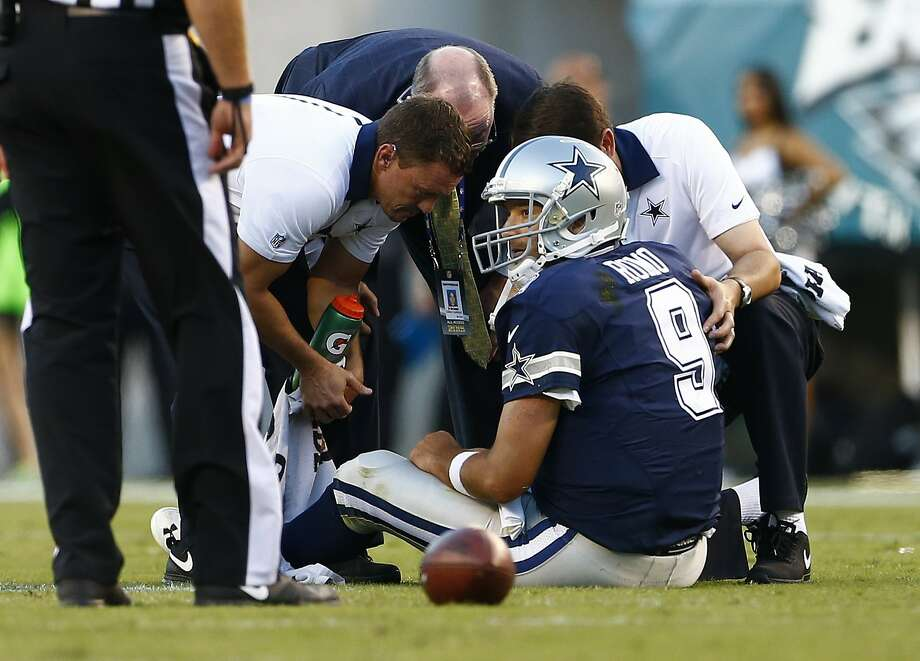 Tony Romo is looked at by trainers after being hurt on a sack. Photo: Rich Schultz, Getty Images