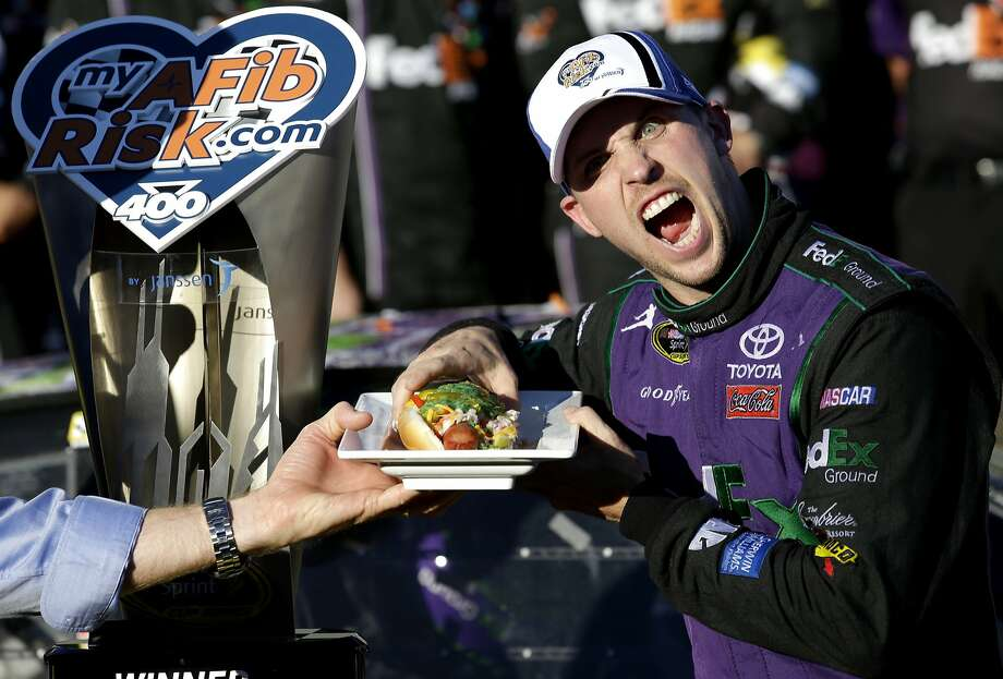 Denny Hamlin eagerly tears into one of his prizes — a Chicago style hot dog. Photo: Nam Y. Huh, Associated Press