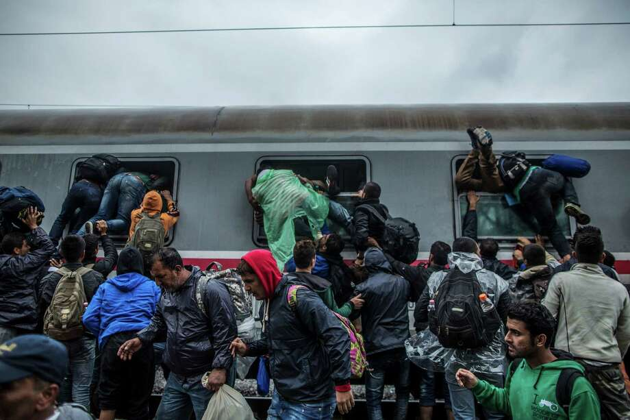 Refugees board a train by climbing through the windows Sunday as they try to avoid a police barrier at a station in Croatia.  Photo: Manu Brabo, STR / AP