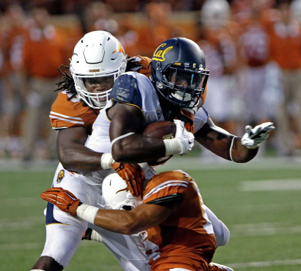 Texas linebacker Malik Jefferson, left, tackles California's Vic Enwere, center, with the help from Kevin Vaccaro, right, during the first half of an NCAA college football game, Saturday, Sept. 19, 2015, in Austin, Texas. California won 45-44. (AP Photo/Michael Thomas)