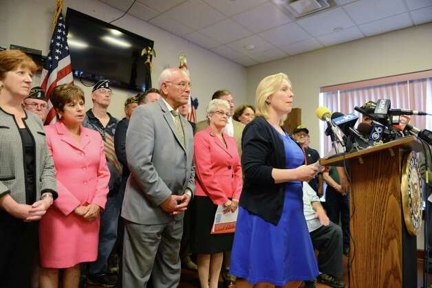 Sen. Kirsten Gillibrand, right, is joined by state and area leaders including Mayor Kathy Sheehan, left, Colonie Supervisor Paula Mahan  and Rep. Paul Tonko and others, right, as she and Rep. Chris Gibson, not pictured, called for passage of legislation that would include veterans who served in the waters surrounding Vietnam among a group presumed to have been exposed to Agent Orange. They spoke on Monday, July 6, 2015, at the Joseph E. Zaloga American Legion Post 1520 in Colonie, N.Y. (Will Waldron/Times Union) Photo: WW / 00032505A