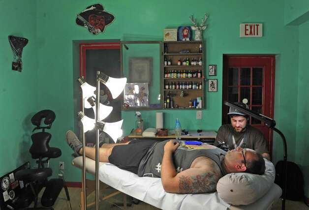 Nicholas Reinert, a local visual artist who now primarily works as a tattoo artist, is giving workshops on all matters of tattoos at the Arts Center of the Capital Region on Wednesday Sept. 9, 2015 in Troy, N.Y.  Nick tattoos Tony Colasurdo of Albany.  (Michael P. Farrell/Times Union) Photo: Michael P. Farrell / 00033288A