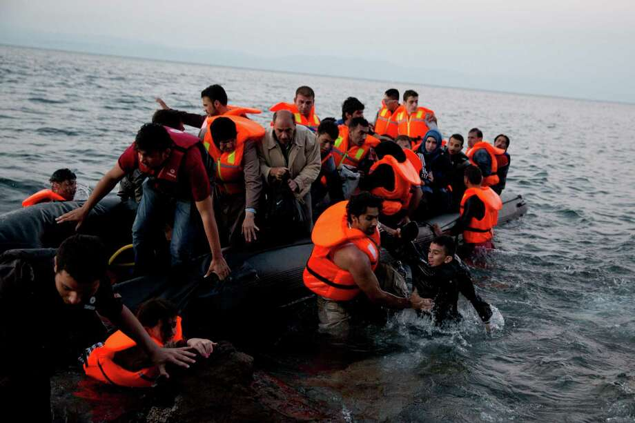 Syrian refugees arrive aboard a dinghy after crossing from Turkey, to the island of Lesbos, Greece, on Sunday, Sept. 20, 2015. Greece's coast guard was searching Sunday for 26 migrants missing off the coast of the eastern Aegean island of Lesbos after the boat they were traveling in sank.(AP Photo/Petros Giannakouris) ORG XMIT: XPG123 Photo: Petros Giannakouris / AP