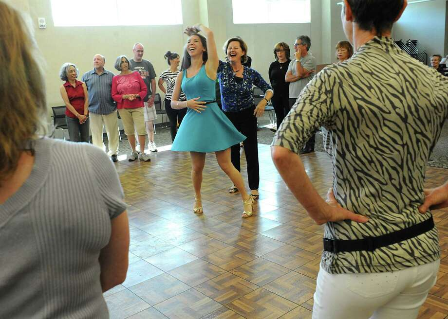 Instructors Jenna Bryfonski, left, and Diane Lachtrupp demonstrate some dance moves during an hour-long dance lesson from Tango Fusion dance company of Saratoga Springs during the Hispanic Heritage Celebration at the Clifton Park Halfmoon Public Library on Sunday, Sept. 20, 2015 in Clifton Park, N.Y. Lachtrupp owns the dance company with her husband. The event was celebrating Hispanic Heritage Month. (Lori Van Buren / Times Union) Photo: Lori Van Buren / 00033374A