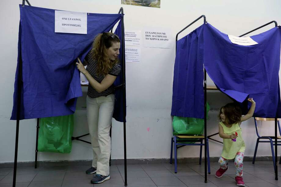 A woman plays with her 3-year old daughter at a polling place Sunday in Athens. Greeks voted in national elections for the third time this year. Photo: Thanassis Stavrakis, STF / AP