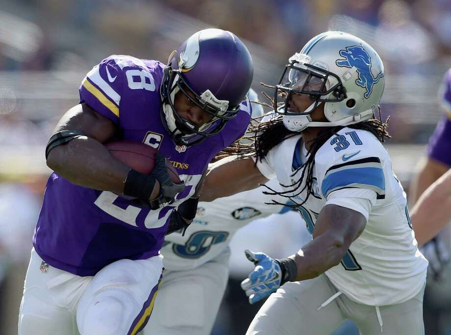 Vikings running back Adrian Peterson, left, gets past the Lions' Rashean Mathis for some of his 134 yards rushing in Minnesota's 26-16 victory at home. Photo: Hannah Foslien, Stringer / 2015 Getty Images