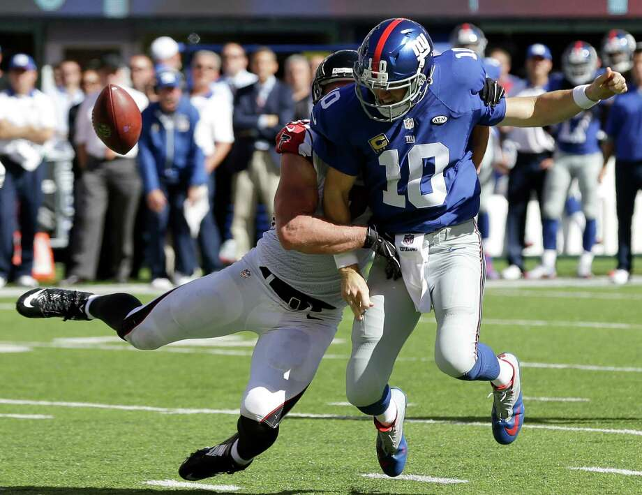 New York Giants quarterback Eli Manning, front, fumbles the ball as Atlanta Falcons outside linebacker Kroy Biermann makes the hit during the second half of an NFL football game, Sunday, Sept. 20, 2015, in East Rutherford, N.J. (AP Photo/Seth Wenig) ORG XMIT: ERU117 Photo: Seth Wenig / AP