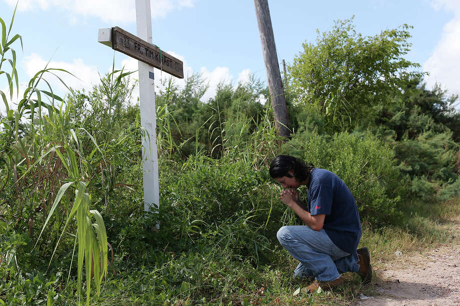 Iraq War veteran Sabastian Vasquez, pays his respect at a memorial for family friend and parish priest, Tim Kinast, on Aug. 6 by the Austwell Pier near Tivoli. Vasquez made three tours and was diagnosed with Post-Traumatic Stress Disorder. Photo: JERRY LARA, Staff / © 2015 San Antonio Express-News