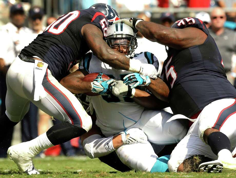 Panthers fullback Mike Tolbert, center, is stopped by Texans inside linebacker Akeem Dent, left, and nose tackle Vince Wilfork. Tolbert carried five times for 31 yards. Photo: Brett Coomer, Staff / © 2015  Houston Chronicle