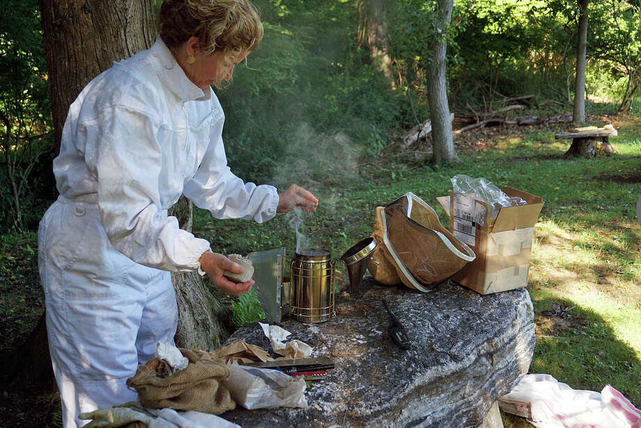Whitney Vose, one of the Fairfield Garden Club's beekeepers, preps the smoker before tending to the Ogden House beehives. Photo: Genevieve Reilly /Fairfield Citizen / Fairfield Citizen