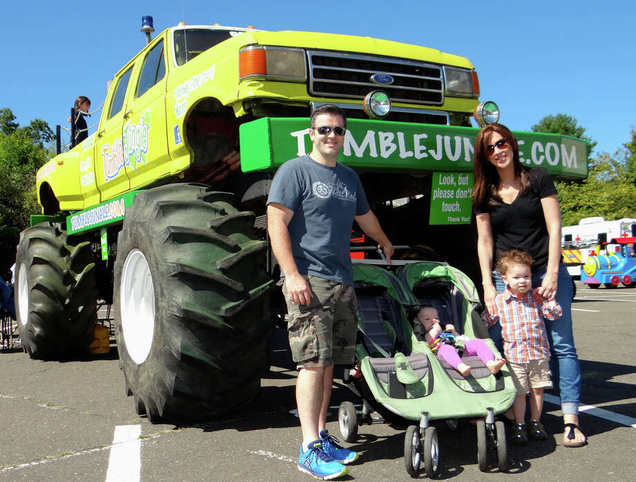 Brendan and Regina Leahy with their children, Silas, 2, and Cora, 8 months in front of Tumble Jungle of Fairfield's monster truck at the Touch-A-Truck sponsored by the Junior Women's Club of Fairfield. Photo: Mike Lauterborn / For Hearst Connecticut Media / Fairfield Citizen