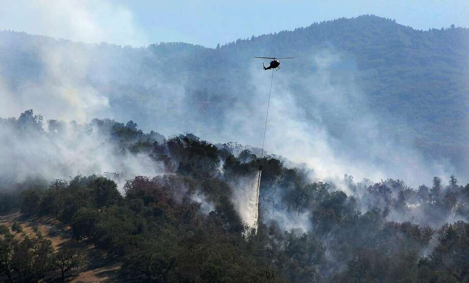 A helicopter makes a water drop on a wildfire hot spot Sunday, Sept. 20, 2015, in Carmel Valley, Calif. The blaze burning north of the community of Jamesburg quickly grew after starting Saturday afternoon, the California Department of Forestry and Fire Protection said. Photo: Vern Fisher, Associated Press