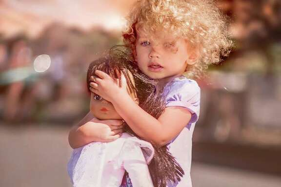"""3-year-old Gracie holds her doll, """"Biggie,"""" protecting her comfort object from seeing the devastation of the Valley Fire, September 2015 (Photo by Diane Derenia)"""