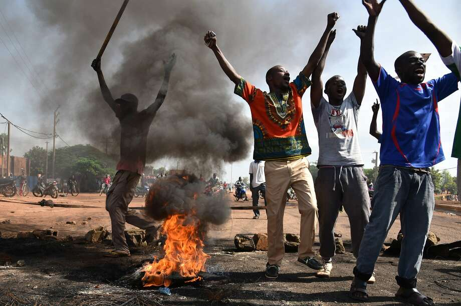 Demonstrators shout slogans next to burning tires in the capital, Ouagadougou, during a protest against a regional proposal to end the crisis. Photo: Sia Kambou, AFP / Getty Images