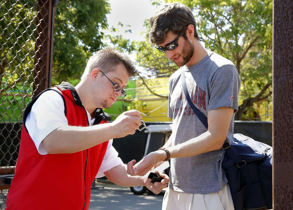 Champ Pederson stamps the wrist of Ken Fockele at the front gate at a Stanford University men's soccer game in Stanford, California, on Sunday, Sept. 20, 2015.