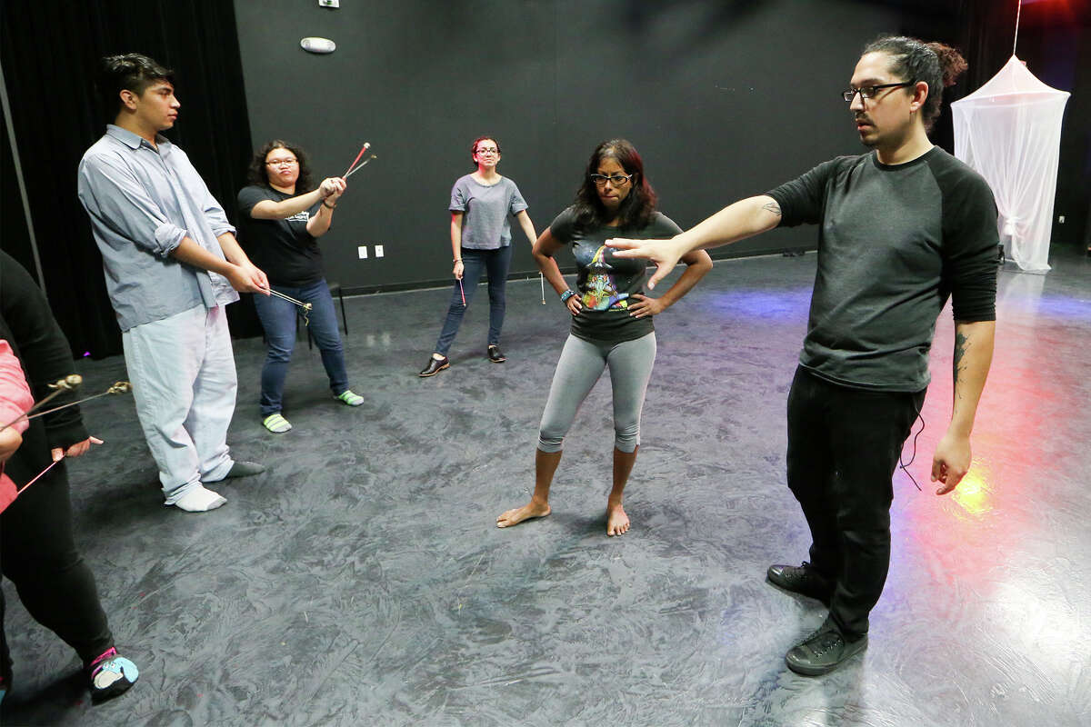 Theater instructor Billy Munoz (from right) and guest artist instructor S.T. Shimi work with the cast during a rehearsal for a multimedia stage production at SAY Si.