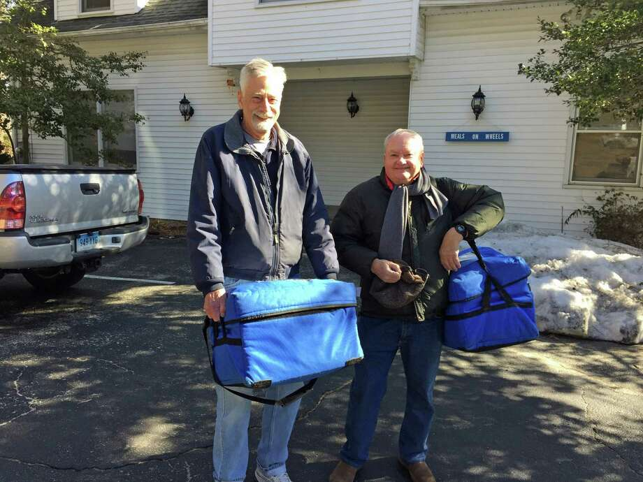 Veteran Meals on Wheels volunteer drivers, from left, Trevor Nightingale and Gerry Boyle, carry the appointed meals in refrigerated blue bags from headquarters at the Womanís Club annex to make their Greenwich delivery rounds. The organization is seeking volunteer drivers to fill out a roster of substitutes when the regular volunteers can't make the trip. Photo: Contributed Photo / Contributed Photo / Greenwich Time Contributed