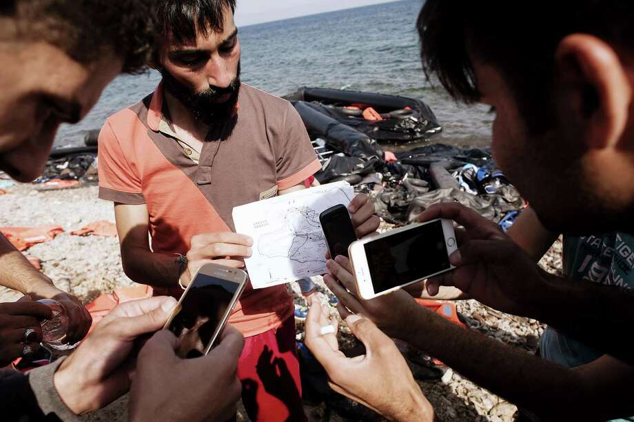Refugees use mobile phones to take pictures of a map Monday upon their arrival on Eftalou beach on the Greek island of Lesbos after crossing the Aegean sea from Turkey.  Photo: IAKOVOS HATZISTAVROU, Stringer / AFP