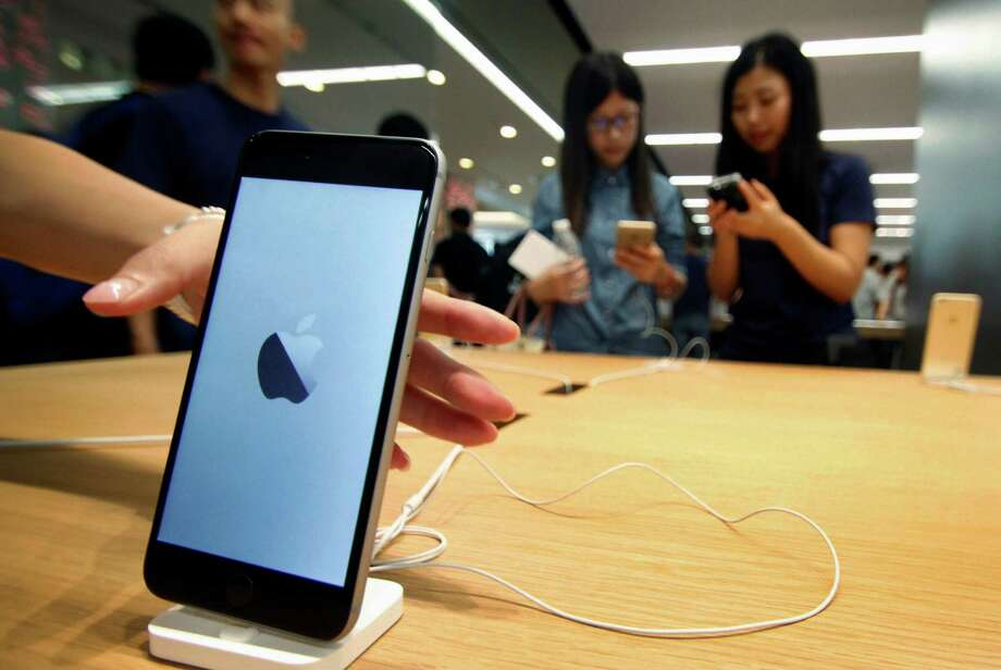 Chinese women try iPhones at a newly opened Apple Store in Nanjing in east China's Jiangsu province. Apple Inc. has removed some applications from its App Store after developers in China were tricked into using software tools that added malicious code in an unusual security breach. Photo: Chinatopix / CHINATOPIX